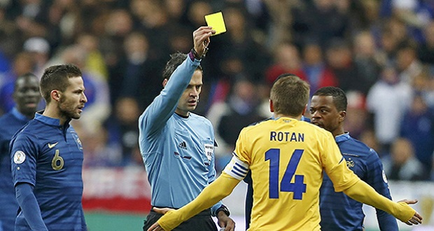 Referee Skomina shows a yellow card to Ukraine's Rotan during their 2014 World Cup qualifying second leg playoff soccer match at the Stade de France in Saint-Denis near Paris