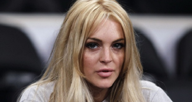 Actress Lindsay Lohan sits courtside before the NBA basketball game between the New York Knicks and the Los Angeles Lakers  in Los Angeles