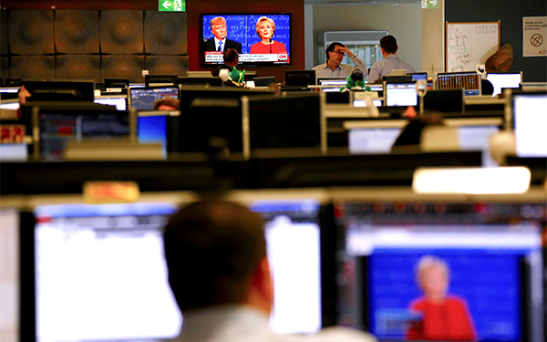 Traders react on the dealing floor of Australia's Westpac Bank in Sydney, Australia, September 27, 2016, as Republican U.S. presidential nominee Donald Trump and Democratic U.S. presidential nominee Hillary Clinton are displayed on screens during the first presidential debate.    REUTERS/David Gray - RTSPKV9