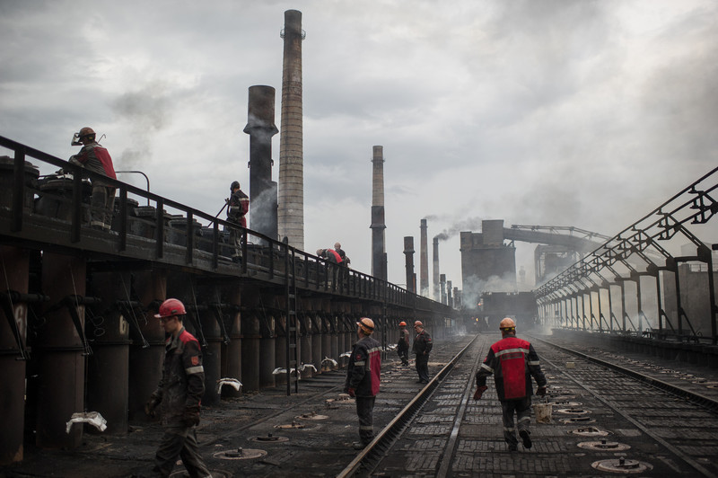 epa04863933 Workers of Avdeevka Coke and Chemical Plant pour refractory mixture into a furnace to ensure safety after-shelling repairs, in the eastern town Avdeevka, near Donetsk, Ukraine, 28 July 2015. Heavy mortar shelling early July 27 has led to two deaths in Avdeevka. Despite a lot of damage caused, Avdeevka Coke and Chemical Plant continues to run.  EPA/ALEXEY FURMAN