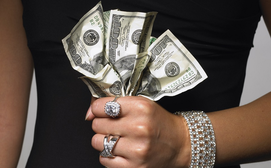 Woman gripping one hundred dollar bills
